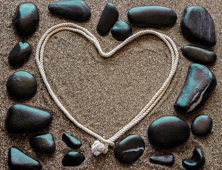bitterness: The concept of love. Black sea stones arranged around a frame, heart shaped. Sandy background. Stock Photo