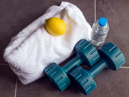 smartness: Concept - sports. Dumbbells are next to a white towel, bottle of water and lemon. Stock Photo