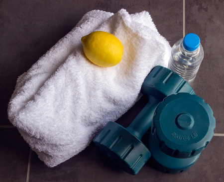 Concept - sports. Dumbbells are next to a white towel, bottle of water and lemon. Stock Photo