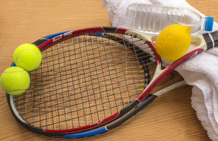 smartness: Concept - sport. Tennis rackets and balls are next to a bottle of water and lemon.