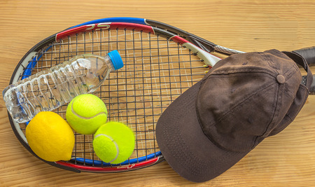 smartness: Concept - sport. Tennis rackets and balls are next to a bottle of water, lemon, and a baseball cap.