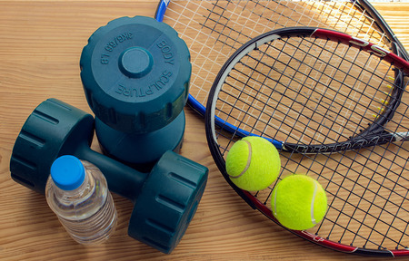 Concept - sports. A bottle of water next to dumbbells, tennis rackets and balls.