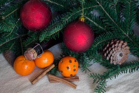 pinecones: holiday concept: cones, tangerine, champagne bottle, spices and red balls. Cinnamon and cloves . Stock Photo