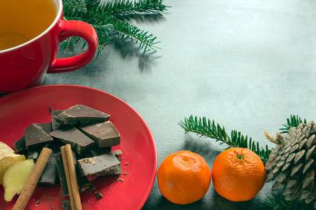 Green herbal tea and dark chocolate in a red ceramic bowl. Concept - hot drinks. Stock Photo