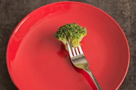 브로콜리 접시에 빨간색입니다. 포크와 나이프. 개념 - 채식주의, 체중 조절, 다이어트, 건강한 식습관.