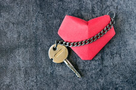 Heart and a key, connected by a chain. Concept - love, romance. Stock Photo - 83302148