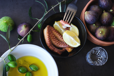 Baked octopus. Traditional Greek snacks. Olive oil and ripe figs. Stock Photo