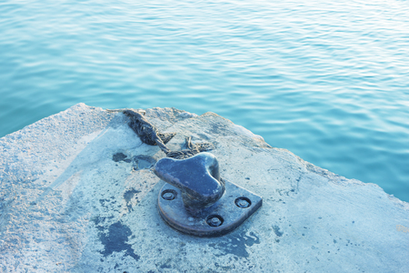 Mooring rope and bollard on sea water  background. Greece.