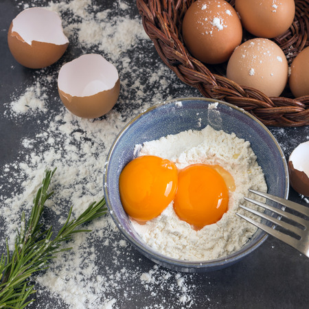 Eggs and flour in the blue bowl. Ingredients for home baking. Delicious Breakfast. Standard-Bild