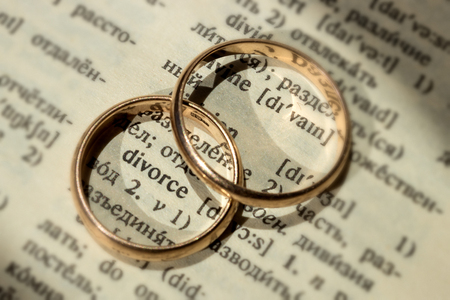 Two separate wedding rings next to the word divorce. The concept of divorce, parting, infidelity . Selective focus.