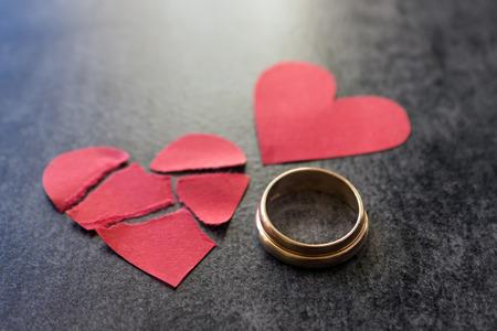 celos: Anillos de bodas y corazón rojo roto. Fondo negro. El concepto de divorcio, separación, infidelidad. Enfoque selectivo. Foto de archivo
