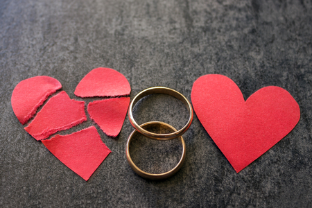 Wedding rings and broken red  heart. Black background. The concept of divorce, parting, infidelity .