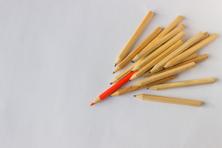 Red pencil standing out from crowd of plenty identical  pencils on table. Leadership, uniqueness, independence, initiative, strategy, dissent, think different, business success concept.