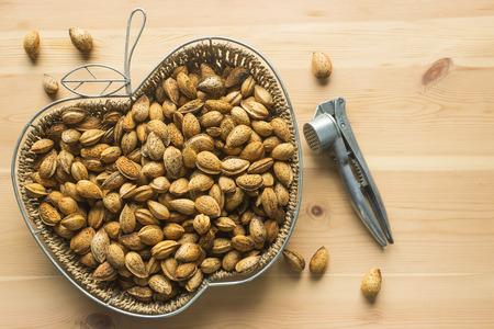 Unshelled almonds in a wicker basket. Metal Nutcracker lying on a wooden table. Stock Photo