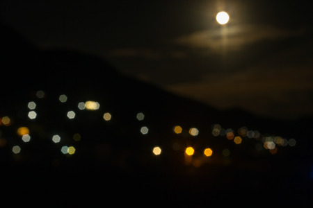 The moon in the night sky. The lights from the village on the hillside and the sky lit by the moon. The image is blurred, bokeh effect. Mountain landscape at dusk.