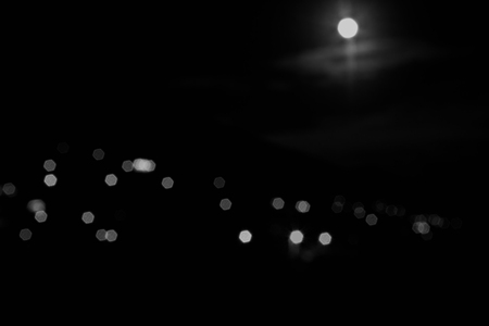 The moon in the night sky. The lights from the village on the hillside and the sky lit by the moon. The image is blurred, bokeh effect. Mountain landscape at dusk. black and white. Stock Photo