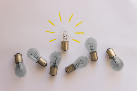 Light bulb with rays  on a white background. Concept-  idea, innovation, business concept, creativity inspiration. Toned.