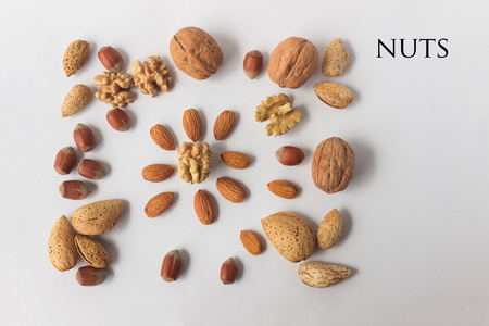 Different types of nuts. A full source of vegetable protein in vegetarianism and raw food. Assorted walnuts, almonds and hazelnuts. Concept - healthy eating. Copy space. Text.