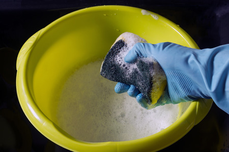 Hand in rubber glove washes sponge in yellow basin. Concept- housework, house cleaning.