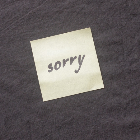 Handwritten note on a dark background. Note of apology- Sorry, please forgive me. Standard-Bild - 98426291