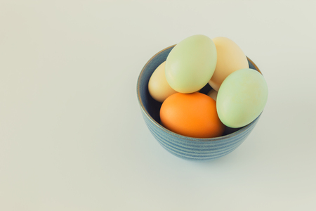 Colorful pastel eggs in a blue bowl on a white background. Concept-Easter, healthy food, organic products, farm products. Copy space. Stock Photo