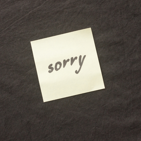 Handwritten note on a dark background. Note of apology- Sorry, please forgive me. Standard-Bild - 99343795