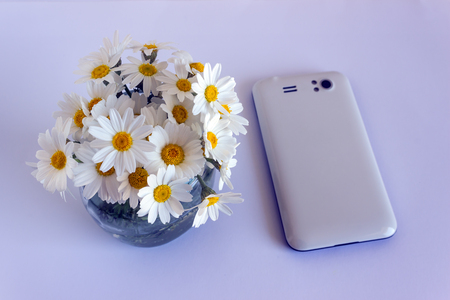 White smartphone next to a small bouquet of daisies.