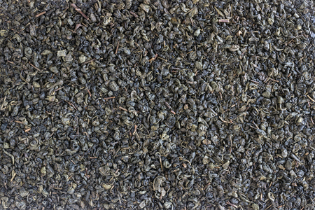 Organic dried green tea leaves . Background, texture.