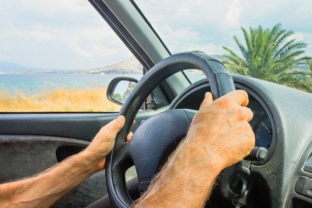 A man behind the wheel of a car with palm trees and sea along the road on a bright sunny day