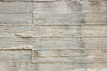 Texture of wooden formwork stamped on a raw concrete wall as background. Stock Photo