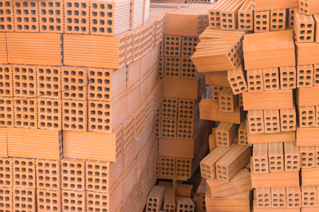 Stack of red clay brick. Warehouse. Storage of products made of bricks. 스톡 콘텐츠