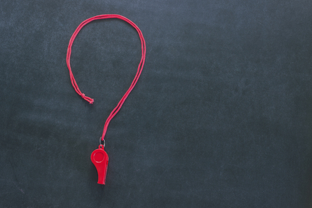 Sports whistle on a red lace. It is laid out in the form of a question mark. Concept- sport competition, referee, statistics, challenge, friendly match.Copy space.