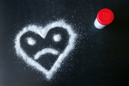 Salt scattered on black surface. Drawn heart with a sad face. Concept- diet, harm to health from excessive consumption of salt and sugar.