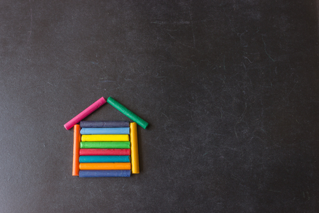 Bright pastel crayons are arranged in the shape of a house on a black school slate. Childrens creativity. Concept- sweet home, back to school, mortgage, your new home.