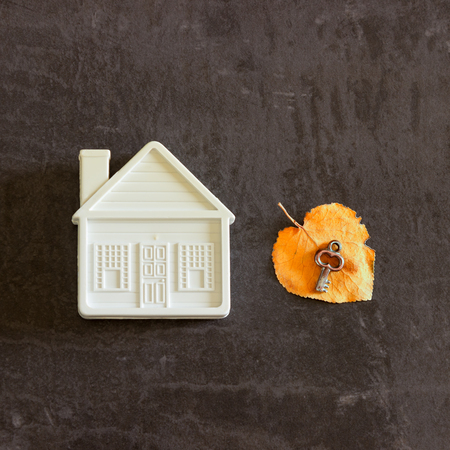 Next to a small toy house is a key on a yellow autumn leaf. Concept- sale,  purchase house, cozy home, safe property.
