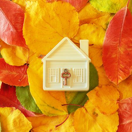 Kleines Spielzeughaus unter bunten Herbstblättern. Konzept- Verkauf, Hauskauf, Wintervorbereitung, gemütliches Zuhause und sicheres Eigentum.