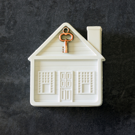 Small toy house with a key. Concept- sale,  purchase house, cozy home, safe property.