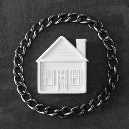 House in chains. Concept  -  risks, lose property,  seize, mortgage. Stock Photo