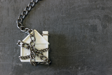 House in chains. Concept  -  risks, lose property,  seize, mortgage. 免版税图像