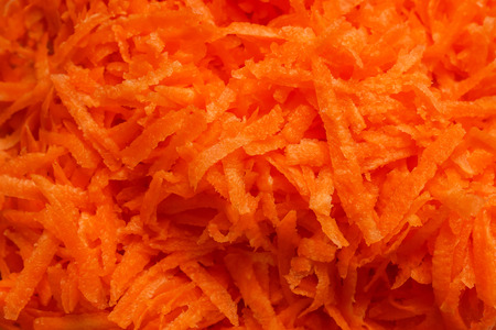 Juicy bright grated carrots. Concept- vegetarianism, raw food, recipe.