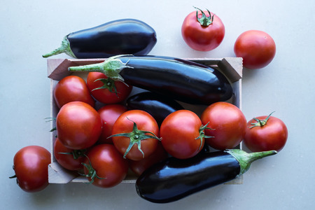 Tomatoes and eggplants  in a wooden crate. Concept- fresh organic vegetables, healthy food from garden.