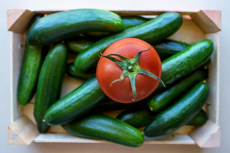 Tomatoes and cucumbers in a wooden crate. Concept- fresh organic vegetables, healthy food from garden. Selective focus. Foto de archivo - 123329479