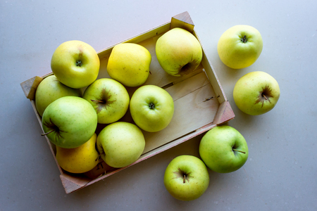 Green apples in a wooden crate. Concept- fresh organic fruit, healthy food from garden. Selective focus. Foto de archivo - 123329482