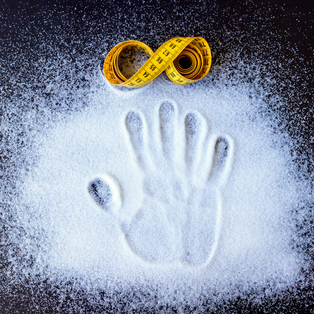 Rolled yellow tape measure and handprint on the scattered sugar. Concept is healthy eating, diet, control and weight loss Stock Photo