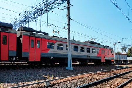 Red suburban train on the station close up. Railway platform with train. Banco de Imagens