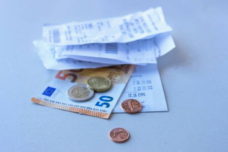 Coins and banknotes lying on a few receipt. Selective focus. Concept - finance.