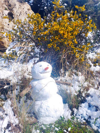 A happy snowman on a background of bright yellow flowers. Blurry background with branches. Waiting for spring. Selective focus.