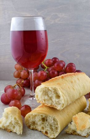 Fresh Baked French Bread, Delicious Red Wine and Fresh Red Grapes Atop a Gray Stone Background.
