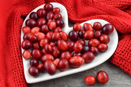 Fresh red cranberries on a heart shaped plate encircled by a textured red kitchen towel. Concept for heart health month and Valentines Day. 版權商用圖片