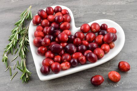 Heart healthy red Cranberries sit merrily on a heart shaped plate. Fresh organic rosemary graces the dark marble background to create a festive holiday or heart health concept.
